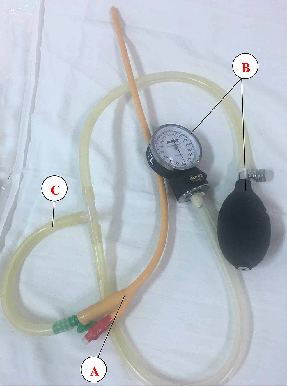 The-device-was-constructed-from-a-Foley-catheter-(Procath,-Ishwari-Healthcare-Pvt.-Ltd.)-(A),-an-ALPK2-sphygmomanometer-(Japan)-(B),-and-plastic-tubes-of-an-appropriate-size-(C).-It-was-completely-sterilized-before-use.