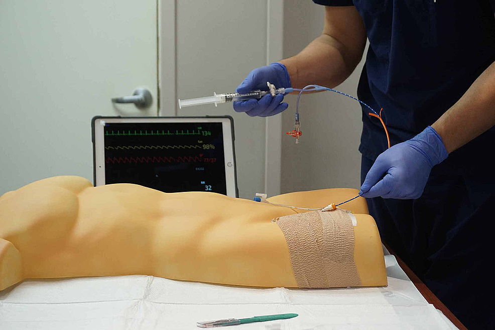 REBOA-insertion-trainer-in-use.--The-participant-is-advancing-the-ER-REBOA-catheter-through-the-introducer-sheath-in-the-simulated-femoral-artery.
