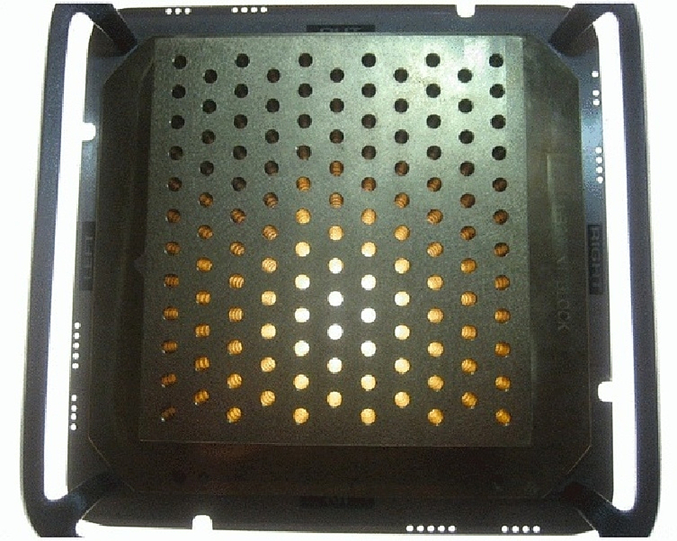 Example-of-a-brass-MLC-based-GRID-used-in-SFGRT-treatment.-Photon-beamlets-pass-through-evenly-spaced-holes-in-the-GRID.-Each-hole-is-1-cm-in-diameter,-with-a-distance-from-center-to-center-of-2-cm.-The-brass-block-is-secured-on-a-metal-tray-and-placed-in-the-location-where-an-IMRT-solid-compensator-would-be-placed.